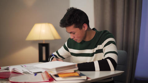 Side view of excited Asian student doing homework indoors. Teenage boy sitting Live Action