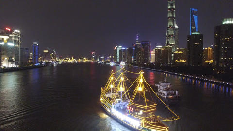 AERIAL shot of tour boats traverse Shanghai's scenic Huangpu River at dusk,China Live Action