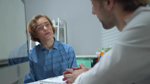 Happy boy talk to doctor in cabinet of hospital Live Action