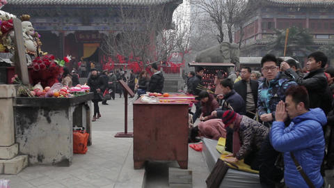 XI'AN, CHINA - FEB 14, 2014: Crowded tourists praying for wealth and health in Live Action