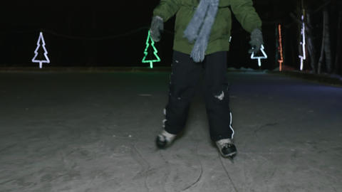 Low section of child skating on ice in the evening at wintertime Live Action