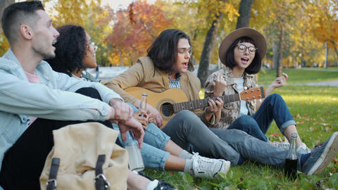 Happy youth singing playing the guitar holding bottles with drinks outside in Live Action