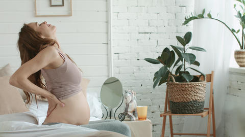 Pregnant woman stretching body in bedroom. Closeup pregnant sitting bed at home Live Action