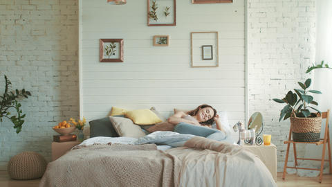 Smiling pregnant woman lying bed at home. Belly mother relaxing morning bedroom Live Action