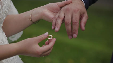 The groom puts the wedding ring on finger of the bride. marriage hands with Live Action