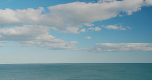 Timelapse. Clouds fast motion above sea. White clouds on the blue sky above calm Live Action