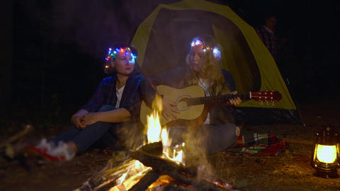 Mom and daughter singing song by guitar front bonfire in campsite at night Live Action