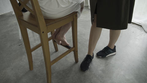 Girl on a chair does makeup by a makeup artist. The legs of two girls in the Live Action