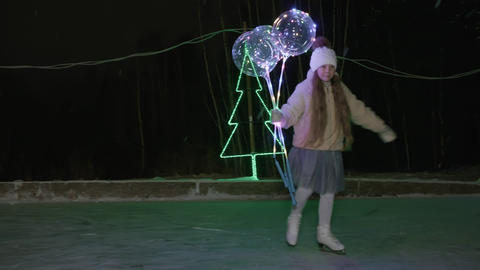 Teenager girl with lighting ball in hands skating on skates on night ice rink in Live Action