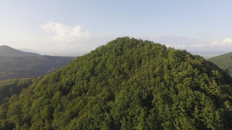 Aerial low over the mountain top with scenic valley view reveal Live Action