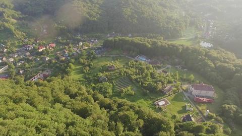Mountain Carpathian village amongst green hills aerial tilt up on sunset Live Action