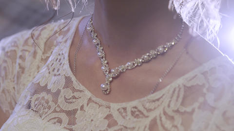 The bride hand straightens the necklace. Bride dresses a necklace Live Action