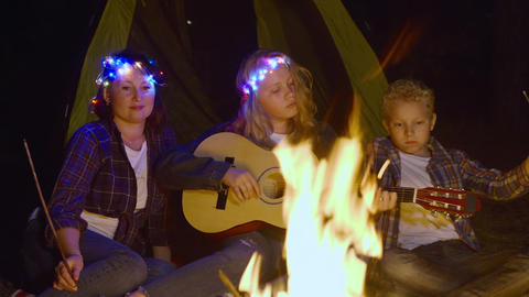 Teenager girl playing on guitar and singing song front campfire in forest hike Live Action