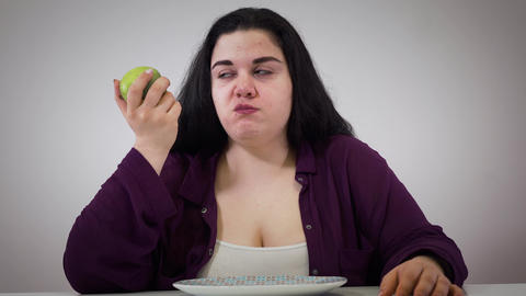 Depressed young Caucasian fat girl eating apple. Fat woman putting fruit aside Live Action