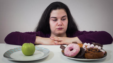 Fat Caucasian woman moving aside plate with apple and taking unhealthy sweets to Live Action