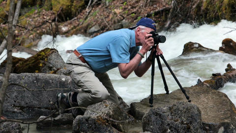 Photographer setting camera on Alaskan flooded river Skagway HD 7166 Footage