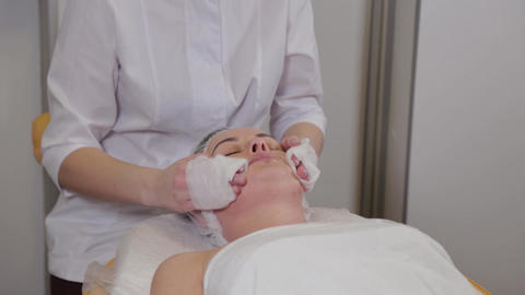 Professional beautician washes face to patient before face cleaning procedure Live Action