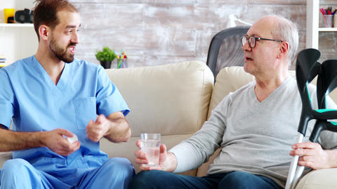 Male nurse giving pills to retired man in nursing home Live Action