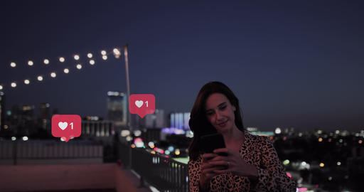 Millennial woman using smart phone at night on roof with animation of likes button on social media Live Action