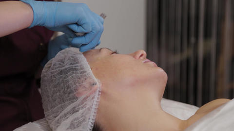 Professional beautician woman performs micronidling facial skin Live Action