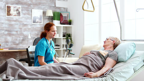 Nurse in retirement home talking with an old lady lying in hospital bed Live Action