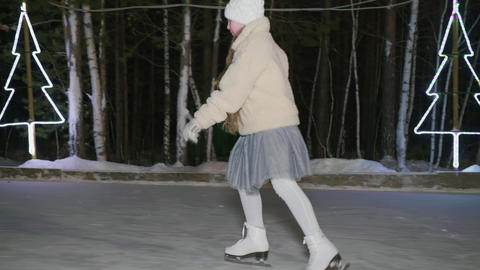 Teenager girl training swallow pose on ice rink in winter park. Young girl Live Action