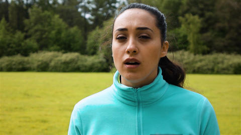 Female jogger out of breath looks around with a subtle smile on her face in slow Live Action