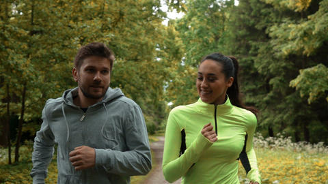 Girl and guy communicating and smiling during morning jog. They running at the Live Action