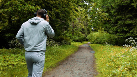 Male runner in warm clothes in autumn park listening to music and hood clothes Live Action