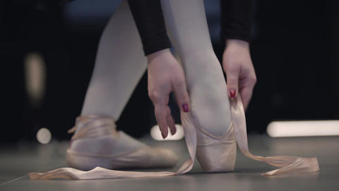 Slowmo of graceful unrecognizable Caucasian ballerina tying up pointes. Elegant Live Action