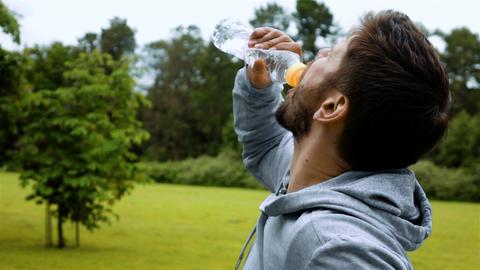 Athlete drinking water from bottle splashing water Live Action
