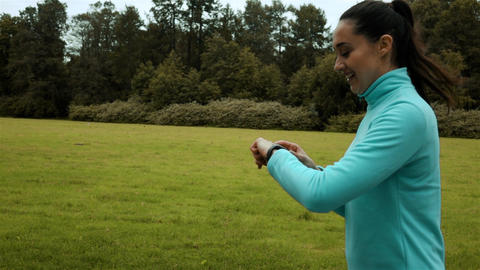 Woman runner using smart watch fitness watch Live Action