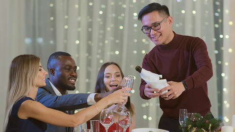 Slow motion a man pours champagne. The multiethnic company celebrates the new Live Action
