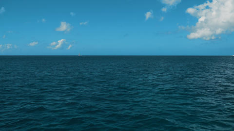 A Wake From a Ship at Sea with Blue Ocean Water, a Horizon, Blue Sky and Clouds Live Action