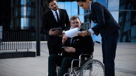 Businessman in a wheelchair with colleagues outside an office building discuss Live Action