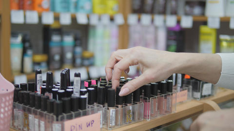 Buying cosmetics in the store. Woman Choosing color cosmetics in the store. Woman uses makeup tester Live Action
