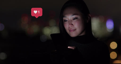 Young Adult Japanese woman using smart phone at night outside, with animation of likes button on Live Action