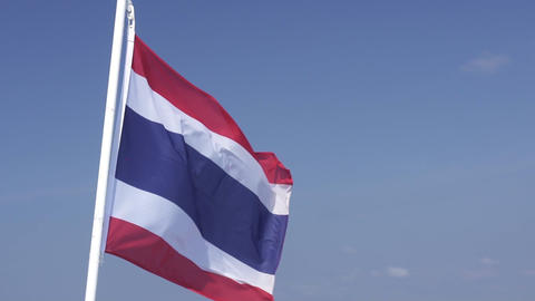 Thai national flag on pole waving in the wind sky background. The national flag of Thailand Live Action