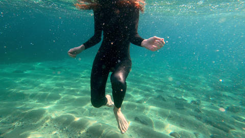 Redhead girl in a black neoprene suit splashes and dance underwater. Sun rays in Live Action