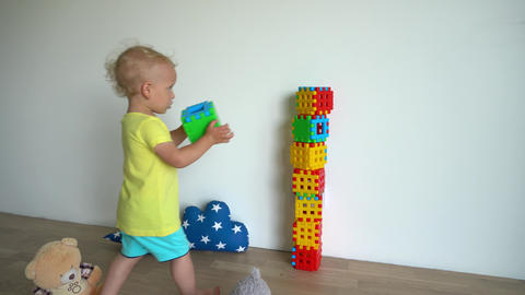 Careful boy child building tower from colorful blocks at home. Gimbal motion Live Action