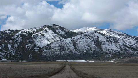 Winter mountain snow over farm land pan HD 2386 Footage