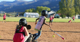 Young girls playing softball rural park slow DCI 4K Footage
