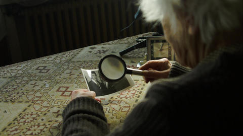 99 Years Old Woman Looking At an Old Photo With Magnifying Glass, Behind Shot Footage