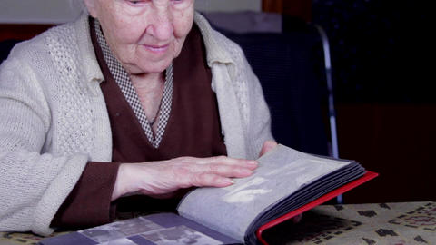 99 Years Old Woman Looking At A Photo In An Old Photo Album, Memories, Pan Live Action