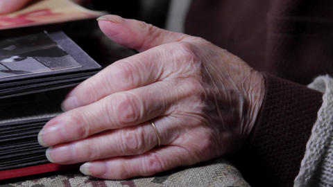 Close Up Of Very Old Woman Hands Flipping Through Photo Album, Pan Footage