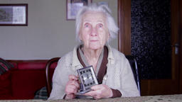 99 Years Old Woman Setting An Old Alarm Clock, Very Old Lonely Woman, Front Shot Footage