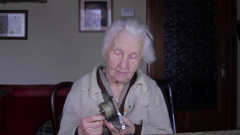 99 Years Old Woman Setting An Old Alarm Clock, Very Old Lonely Woman, Tilt Down Footage