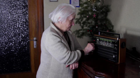 99 Years Old Woman Turning The Buttons Of An Old Radio And Listening Live Action