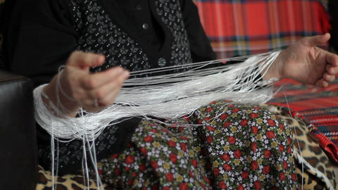 Traditional manual yarn weaving. Woman in local dress wraps fabric yarn Live Action