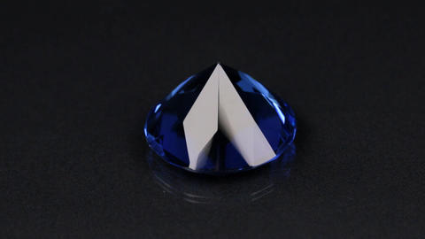 Blue diamond with shiny faces on a black background. Rotation and approximation Live Action